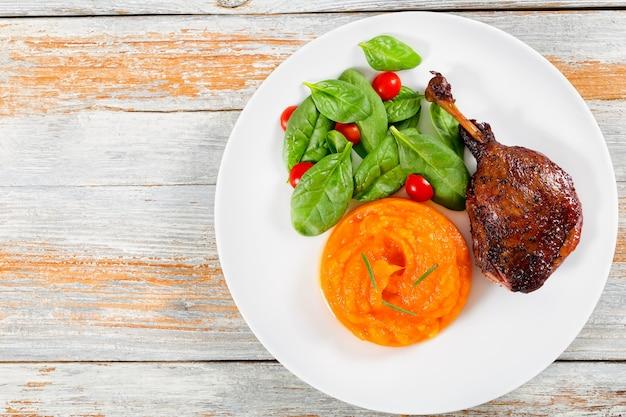 Жареная утиная ножка на блюде со шпинатом и тыквенным пюре