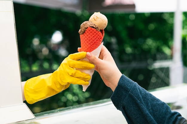 Рука дает мороженое в красном конусе для молодой женщины. продам мороженое на природе. покупка мороженого в парке.