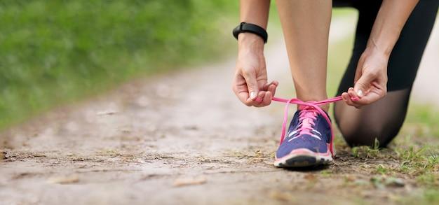 スニーカーを実行している靴紐を結ぶ若いフィットネス女性。健康に合う生活。