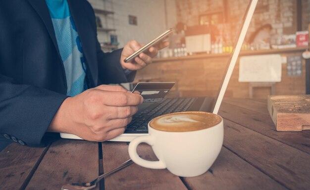 カフェショップでコーヒーを飲み、スマートフォンを使ってクレジットカードを持っているビジネスマン