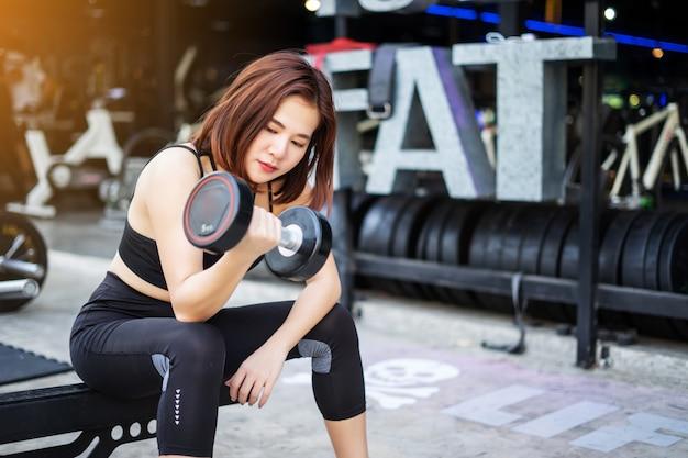 Молодая женщина фитнеса выполняет тренировку с тренировкой фитнес спортзал. женщины с гантелями.