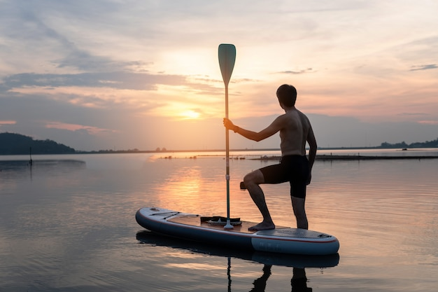 平らで暖かい静かな川に日没で漕ぐスタンドアップパドルボーダーのシルエット。