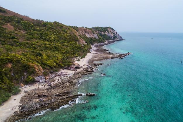 海の波、ビーチ、岩が多い海岸線と美しい森の空中平面図。
