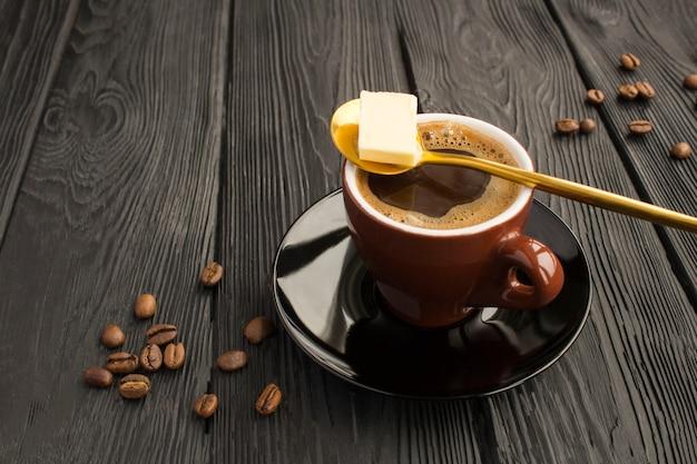 Пуленепробиваемый кофе кето диета энергетический напиток на черной деревянной поверхности. крупный план.