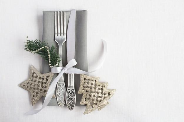 Сервировка стола рождества на серой салфетке на белой предпосылке ткани. вид сверху. копировать пространство