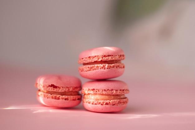 ピンク色の光沢のある太陽光線とピンクのカラフルなマカロンおいしいフランスクッキー