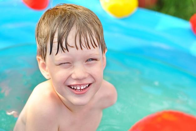 スイミングプールで夏に青い水の中の金髪の少年の笑顔