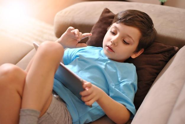 Маленький малыш мальчик на диване и проведение планшета