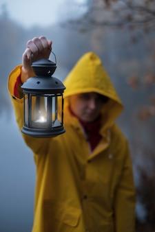 暗い霧の秋の霧で懐中電灯と明るい黄色のレインコートの少女
