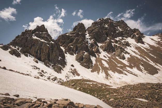 Система тянь-шаня в казахстане недалеко от города алматы. скалистые вершины покрыты снегом и ледниками в середине лета под облаками