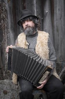 Портрет кудрявого взрослого мужчины с бородой, в шляпе сидит со старым аккордеоном на деревянном фоне в деревне