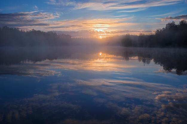 森の霧深い湖の夜明け。青い空と太陽が水に反映
