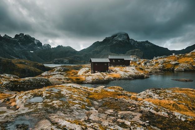 Суровая природа лофотенских островов норвегии. горный осенний пейзаж. поход на гору мункен, деревянные дома, укрытие у озера на фоне грозового неба.