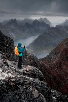 Человек стоит на вершине горы и делает снимок на свой мобильный телефон