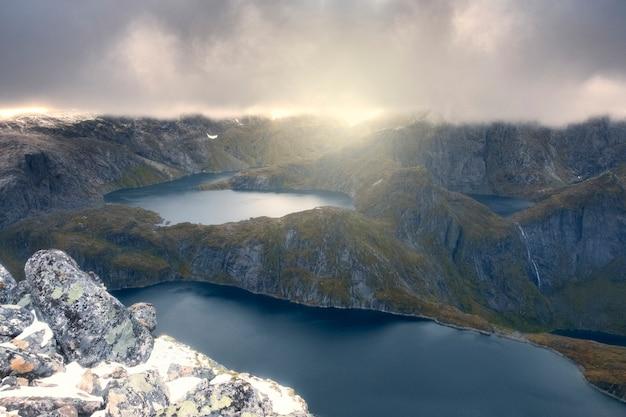 Пейзаж суровой норвегии, лофотенских островов. грозовые тучи и солнечный свет над озерами и горами. поход на гору мункан