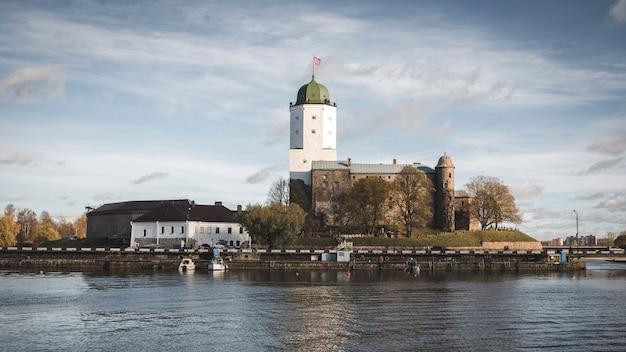Высокая старая башня святого олафа из выборгского замка на острове отражается в воде финского залива в солнечный осенний день