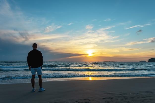日没時に熱帯のビーチで男旅行者