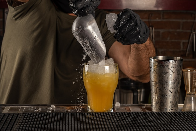 Бармен в баре наливает лед в апельсиновый алкогольный коктейль