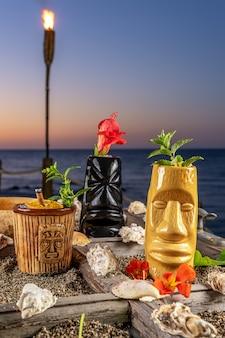 日没時に海の背景に別のトロピカルティキカクテル