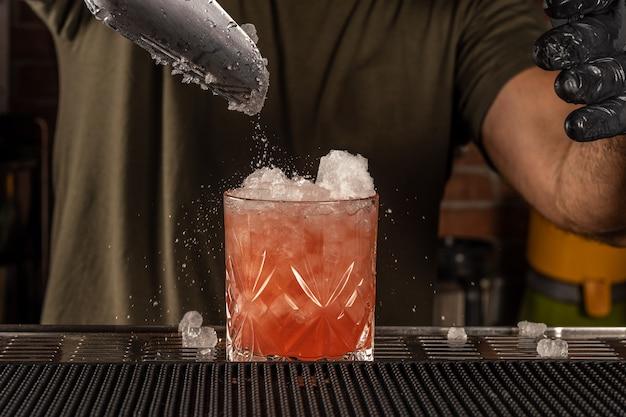 Бармен в баре готовит алкогольный коктейль со льдом