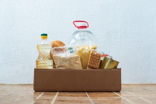 Картонная коробка с различными крупами, консервами, маслом и водой