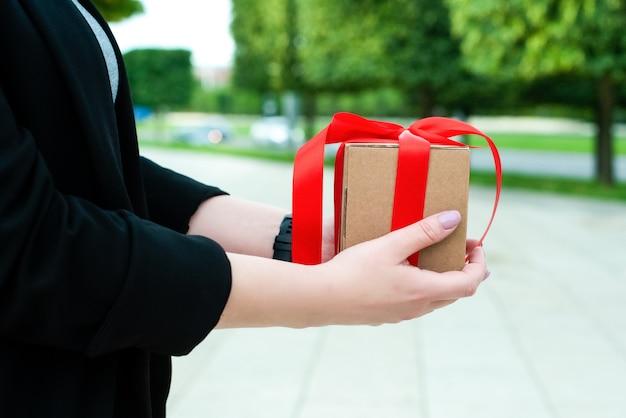 女性の手が贈り物を持っています。赤いリボンとタグが付いたクラフトボックスに入っています。閉じる。外側。美しい朝市の自然。休日の概念、父の日、母の日、誕生日、ウェディング