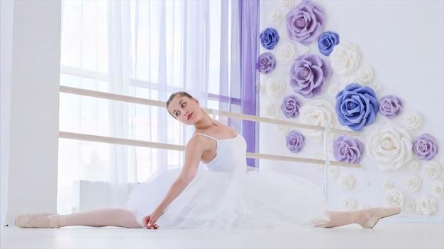 Балерина в белой пачке и пуантах тянется, сидя на шпагате в балетном классе.