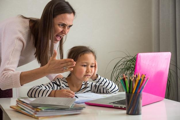 オンラインレッスン中の怒った母親と退屈な娘
