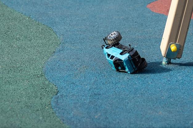 壊れた子供のおもちゃが壊れたおもちゃの車、プレイグラウンドに横たわっています