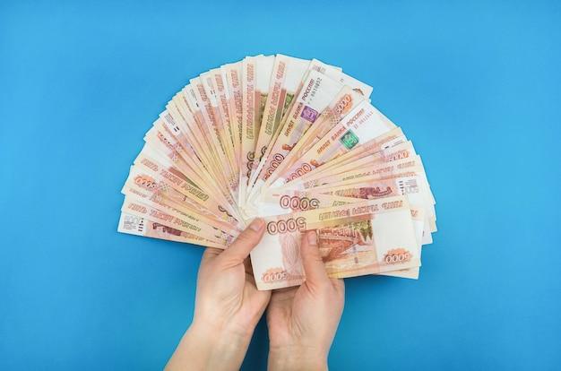 Девушка держит деньги в руках на синем фоне