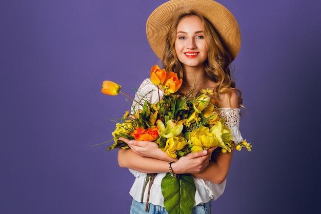 麦わら帽子、白い綿のシャツに座って、素晴らしい春の花の花束を保持しているかなりかわいいブロンドの女性のスタジオファッションポートレート。スタイリッシュなレトロな衣装を着ています。