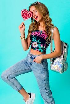 カラフルなピンクのドーナツを保持している美容金髪ファッションモデルの女の子。お菓子、デザートで面白いうれしそうな女性。ダイエット、ダイエットのコンセプトです。ジャンクフード。明るい色。