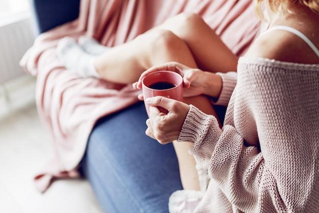 ソファの上のコーヒーのカップを持つ美しい女性