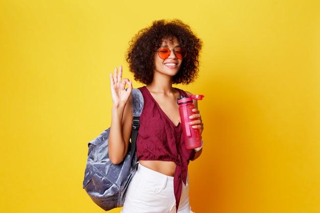 黄色の背景のスタジオでポーズをとってピースサインでスタイリッシュな夏の服装で幸せな遊び心のある黒人女性。水のボトルを保持しています。アフロの髪型。健康的な生活様式。