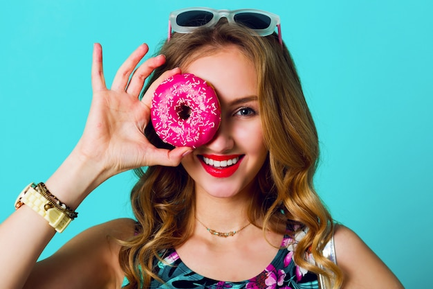 カラフルなピンクのドーナツを取って美容金髪ファッションモデルの女の子。お菓子、デザートで面白いうれしそうな女性。ダイエット、ダイエットのコンセプトです。ジャンクフード。明るい色。