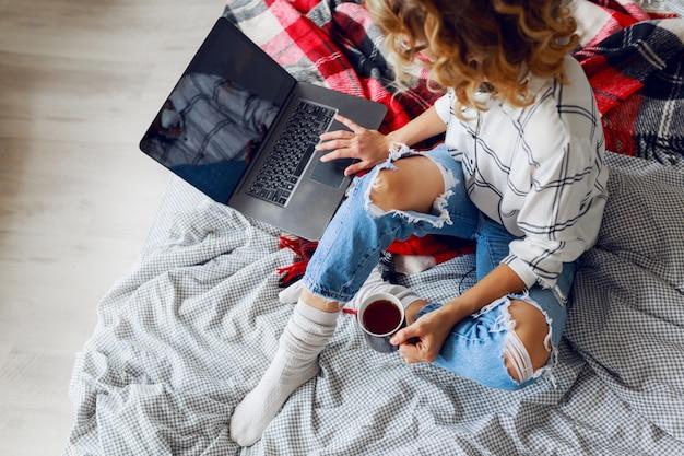 Красивая женщина с чашкой кофе и ноутбуком
