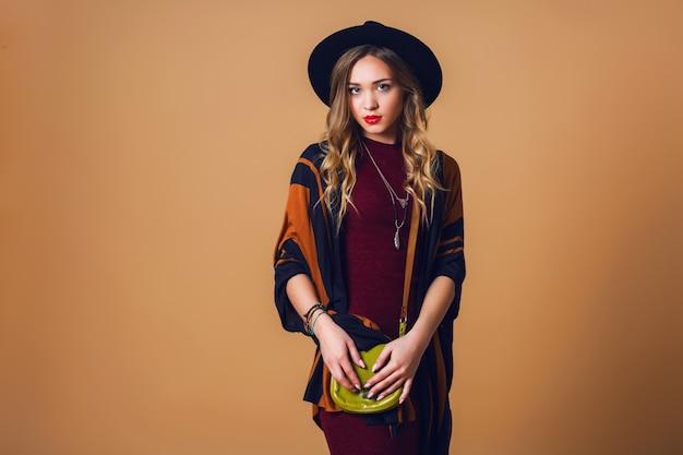 スタジオは茶色のストローポンチョ、ウールの黒のトレンディな帽子、カメラ目線の丸いメガネの若い新鮮なブロンドの女性の肖像画を閉じます。グリーンレザーにバッグがありました。