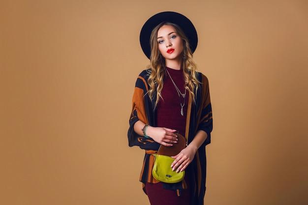 茶色のストローポンチョ、ウールの黒のトレンディな帽子、カメラ目線の丸いメガネの若い新鮮なブロンドの女性のスタジオポートレート。グリーンレザーにバッグがありました。