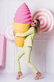 スタイリッシュなエレガントなブロンドの女性がカジュアルなパステルスーツのお菓子と一緒にスタジオでポーズします。キャンディとマカロンのオブジェクトの背景。柔らかなパステルカラー。