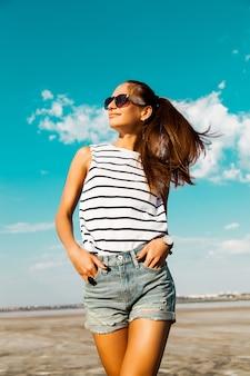 Довольно счастливая девушка в полосатой футболке и джинсовых шортах позирует в очках на пляже