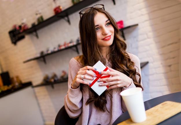 彼女の誕生日やデートを楽しんでいる贈り物とスタイリッシュなモダンなカフェで女性を祝っています。