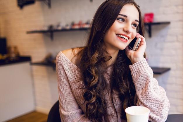 Женщина, набрав написать сообщение на смарт-телефон в современном кафе. подрезанное изображение молодой милой девушки сидя на таблице с кофе или капучино используя мобильный телефон.