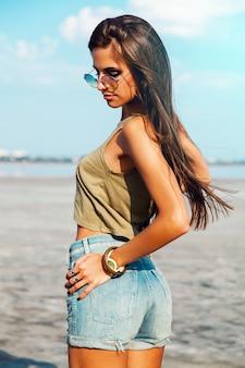 きれいな女性が太陽が降り注ぐビーチでポーズします。クールなサングラスをかけています。