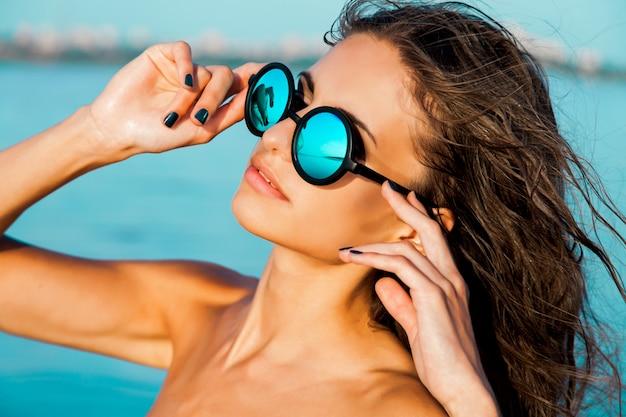 メガネと青い水と太陽が降り注ぐビーチで濡れた髪のスタイリッシュな美しいセクシーな女の子の肖像画を閉じます。日光浴をして、残りをお楽しみください。