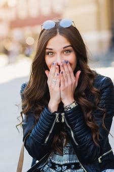 楽しい、感情的な顔をして笑っているスタイリッシュな若い女性のアウトドアファッションの肖像画。都会のストリートスタイル。春または秋の服。