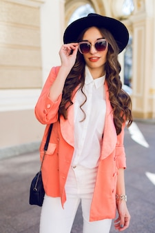 Наружная высота моды портрет сексуальный стильный случайные женщины в черной шляпе, розовый костюм, белая блузка позирует на старой улице