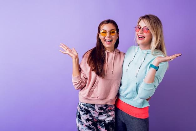 驚きの顔で二人の女の子が紫色の壁の上にとどまっています。おしゃれなパーカーとかっこいいメガネを着ています。