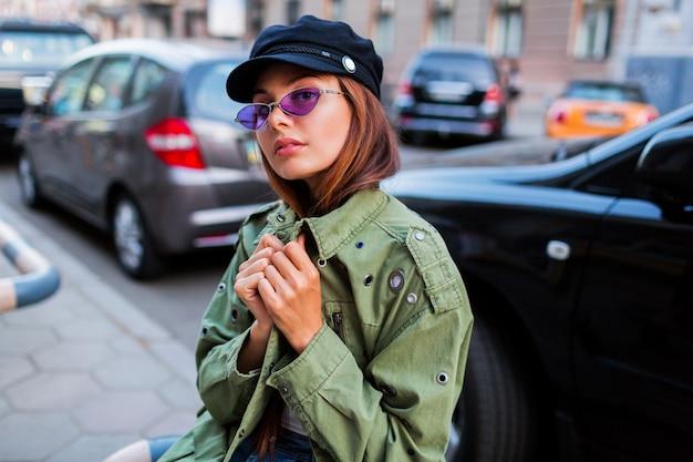 カメラ目線の美しい少女。道路の近くに座っている緑のジャケットでファッショナブルな女性の肖像画を閉じる