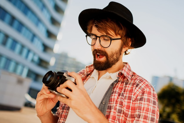 Возбужденный мужчина с бородой с интересом использует ретро пленочную камеру, делает фотографии