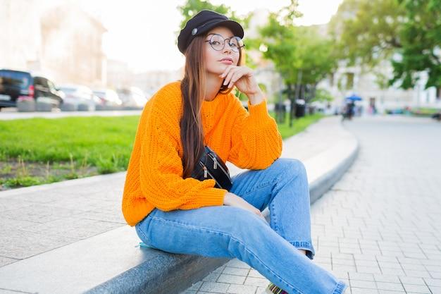 歩道の上に座って、夜を楽しんでいるロマンチックな夢のような女性のアウトドアライフスタイルのイメージ。